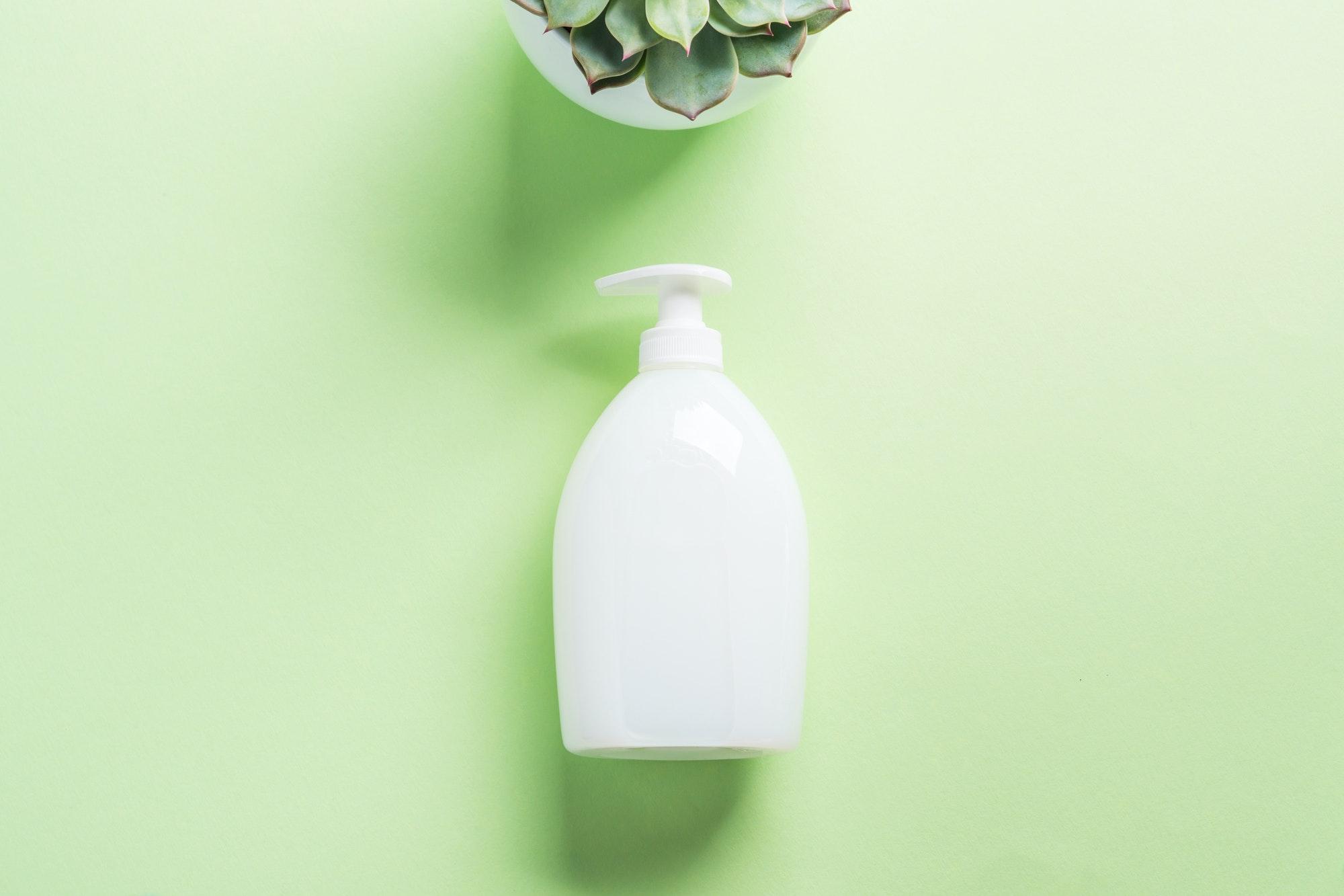 White natural soap bottle on pastel green